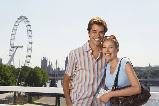 Young vacationing couple posing by Thames River portrait