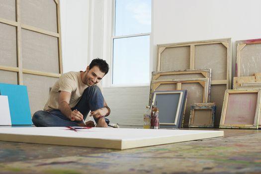 Artist painting on canvas lying on studio floor