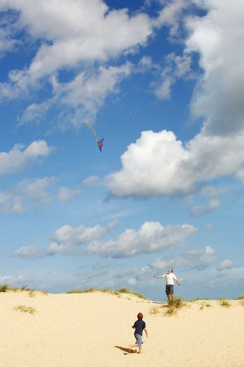Father and Son Flying Kite on sand dune on beach