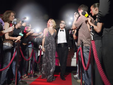 Celebrity couple walking down red carpet photographed by paparazzi
