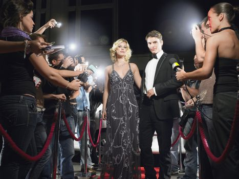 Celebrity Couple walking down red carpet journalists around