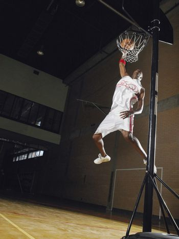 Basketball player slam dunking low angle view