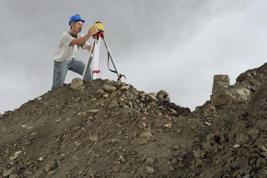 Surveyor using theodolite on site