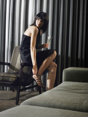 Woman with champagne glass adjusting high heel in living room