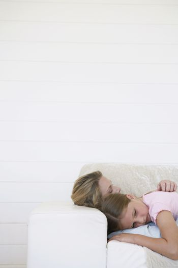Mother hugging daughter on sofa head and shoulders