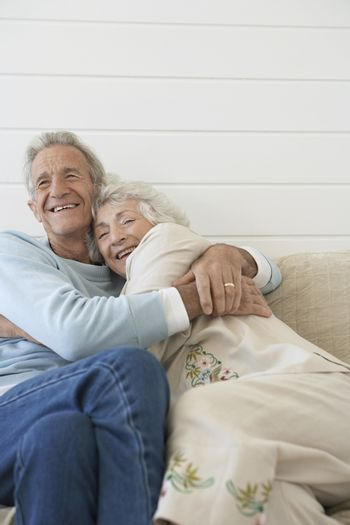 Senior couple embracing sitting on couch