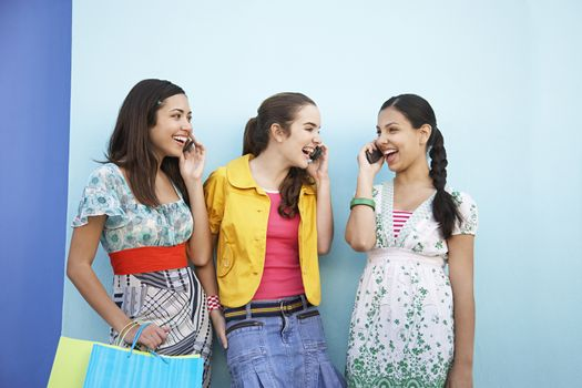 Three teenage girls (16-17) using mobile phones standing in front of blue wall