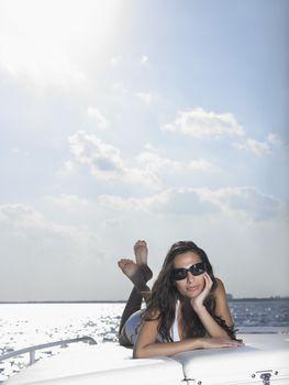 Young woman in bikini lying on cushions on yacht