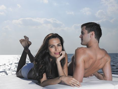 Young couple relaxing on cushions on yacht