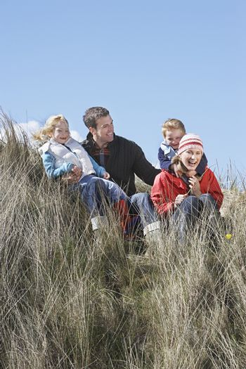 Parents with two children (4-6) sitting in grass