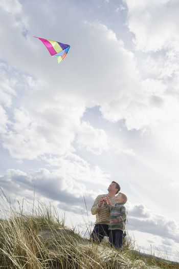 Father and son (5-6) flying kite on dunes