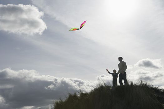 Silhouette of girl and father flying kite on dunes