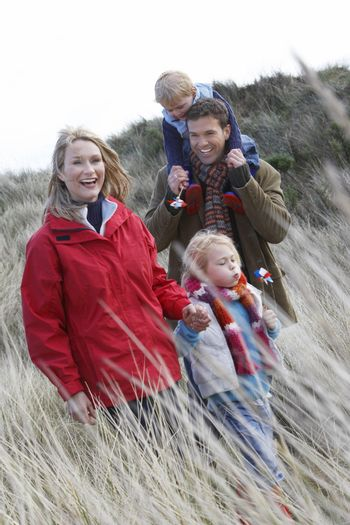 Parents with two children (3-6) walking in long grass