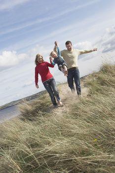 Parents lifting daughter (5-6) on sand dunes