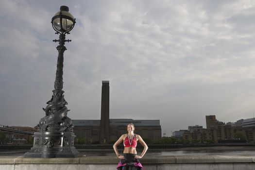 Triathlon athlete standing by river embankment London England