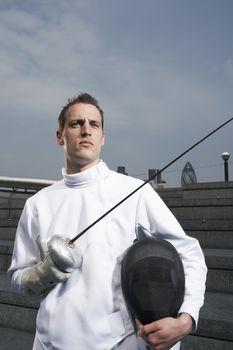 Fencer holding sword outdoors portrait