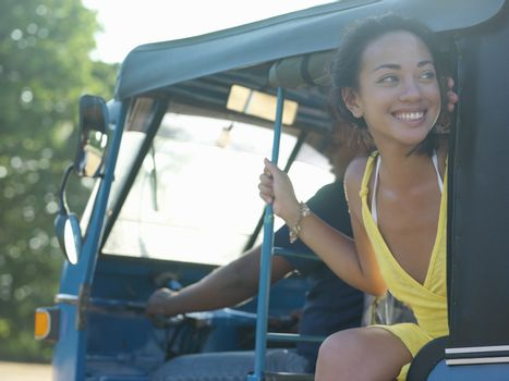 Young woman sitting in vehicle looking away smiling