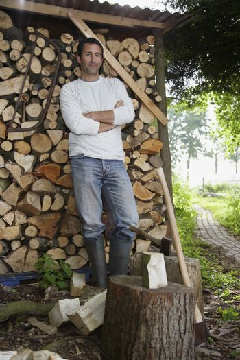 Man standing beside axe at timber shed portrait