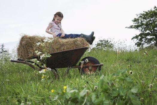 Girl (5-6) sitting on hay in wheelbarrow in field