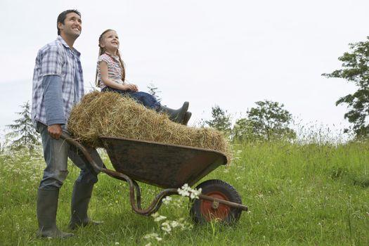 Father pushing daughter (5-6) on wheelbarrow in field