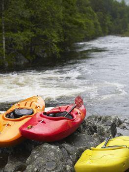 Three kayaks by river