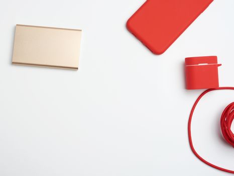 golden power bank, red smartphone and cable in textile braid on