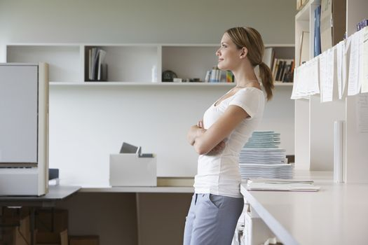Office worker leaning on bench in office side view