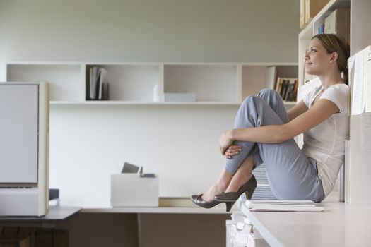 Office worker sitting on bench in office side view