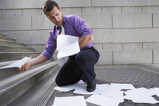 Man collecting spilled paperwork from steps