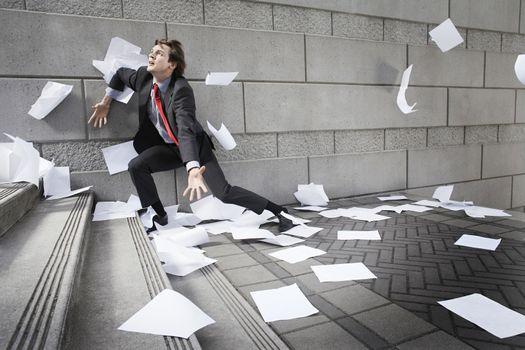 Busines man catching falling paperwork on steps