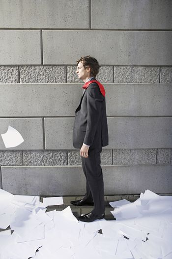 Business man surrounded by paper material beside wall