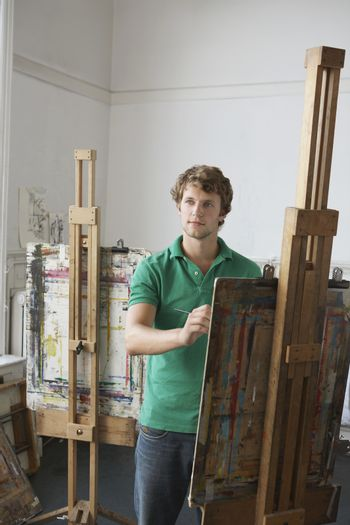 Artist painting at easel in studio