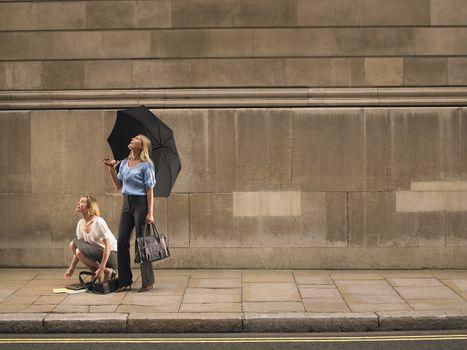 Two women on sidewalk looking up