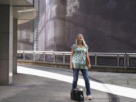 Woman standing on sidewalk looking up