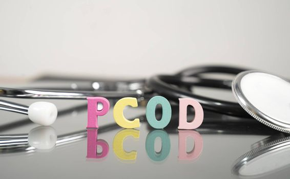 PCOD or Polycystic ovary syndrome medical or healthcare illness Concept showing letters and stethoscope as background
