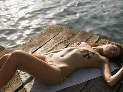 Young woman sunbathing on jetty elevated view