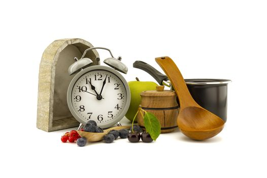 Culinary still life with old-fashioned alarm clock, wooden spoon, pot, apple, jar of honey, cherries, red currants and blueberries over white background with copy space