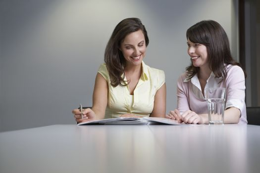 Two women reading papers at desk