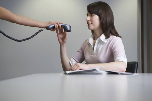 Woman handing over phone receiver to colleague at desk