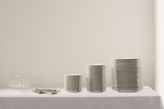 Stacks of plates cutlery and wineglasses on table