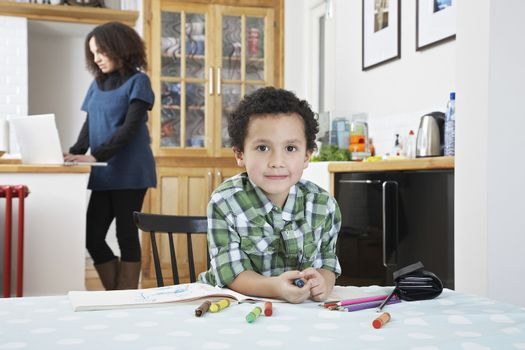 Boy (5-6) colouring in colouring book mother using laptop in background