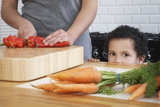 Boy assisting mother chopping pepper