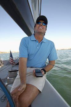Sailor using navigation equipment on boat