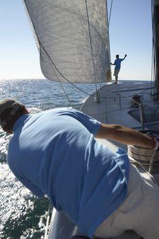 Sailors on yacht in ocean