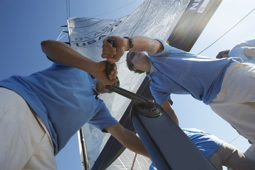 Men raising sail on yacht view from below