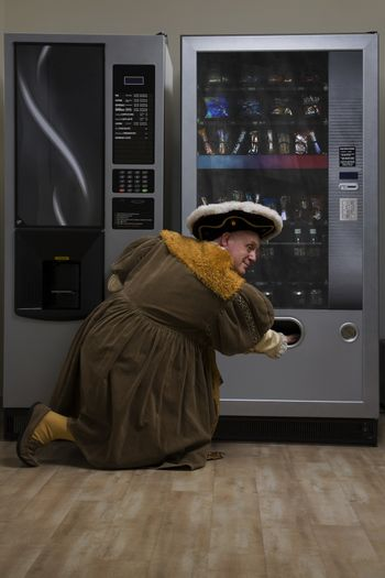 King Henry VIII using vending machine in cafe