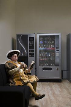 King Henry VIII reading on sofa near vending machine