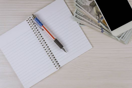 Notebook with blank pages a pen on smartphone workspace office table supplies and us dollars