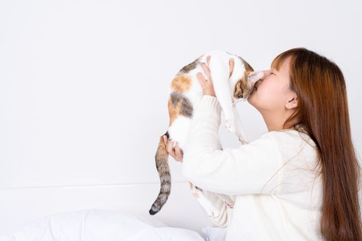Woman at home holding and kissing her lovely fluffy cat. Multicolor tabby cute kitten. Pets and lifestyle concept.
