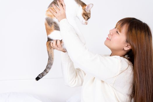 Woman at home holding her lovely fluffy cat. Multicolor tabby cute kitten. Pets and lifestyle concept.